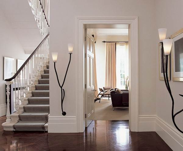 Белая широкая напольная планка выполнена в таком же цветовом решении, что и стены. Это визуально увеличивает высоту комнаты и облагораживает интерьер.