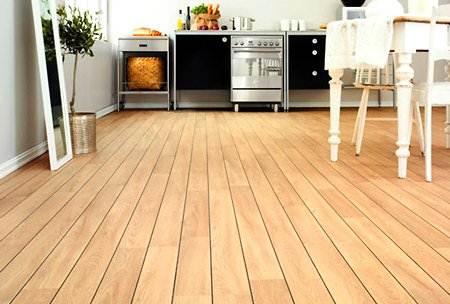 Фото: деревянный пол на кухне – это один из уместных вариантов использования экологически чистых, натуральных строительных материалов в помещении для приготовления и приема пищи, но он требует тщательного ухода и защиты.