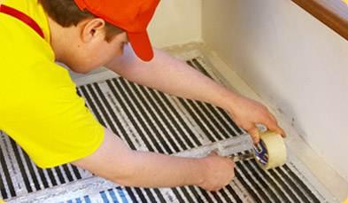 Фото: монтаж пленочного теплого пола под линолеум – для его фиксации нужен односторонний или двусторонний клеящий скотч для напольных покрытий.