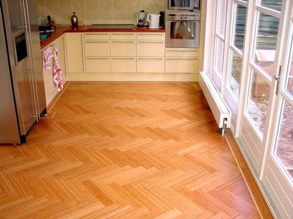 Фото: Постелив деревянный пол на кухне, будьте готовы к постоянному уходу за ним и периодического обновления его поверхностной защиты ЛКМ, мастиками, восками.