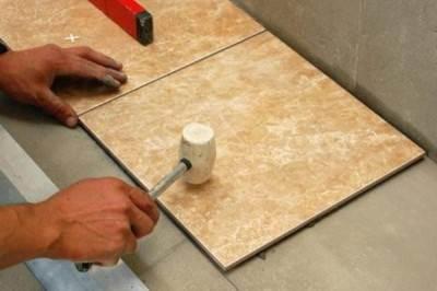 Использование молотка из резины для выравнивания кафеля