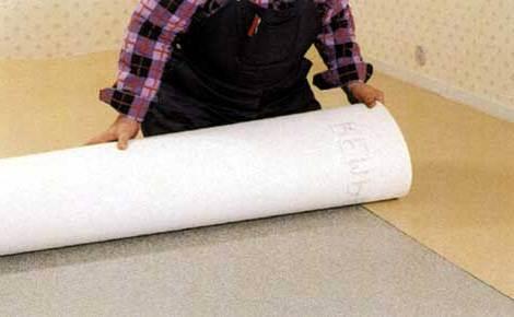 На фото – процесс укладки линолеума на бетонный пол.
