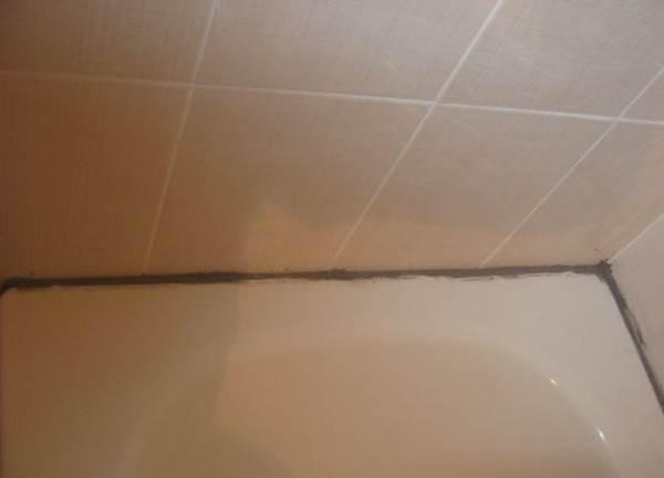 На фото изображено, как заделывались стыки на ванной старым методом.