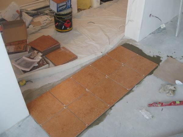 На фото кафель укладывается на бетонное основание. Его толщина в этом случае не имеет никакого значения: деформирующие нагрузки примет перекрытие.