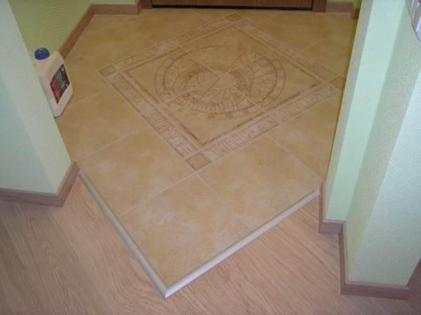 На фото один из самых распространённых способов решения вопроса, чем закрыть стык между плиткой и ламинатом