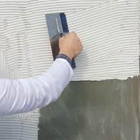 Нанесение клеевого состава на стену.
