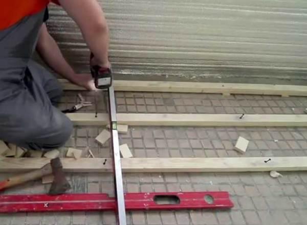 При изготовлении лаг необходимо использовать водяной уровень и деревянные подкладки