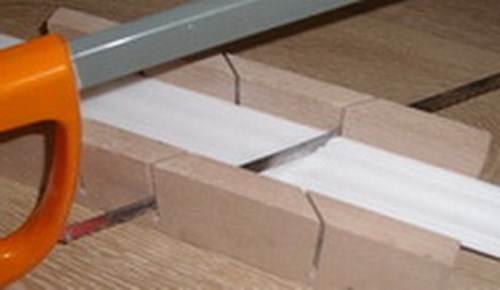 Процесс резки пластикового бордюра при помощи стусла.