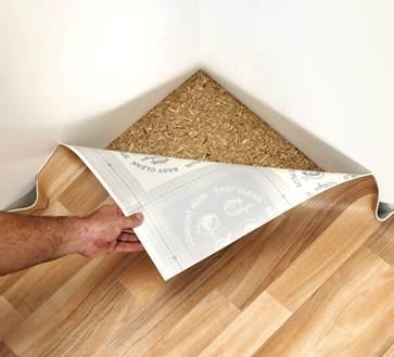Расстилают материал на пол с учетом небольшого запаса, который сначала выправляют на стены