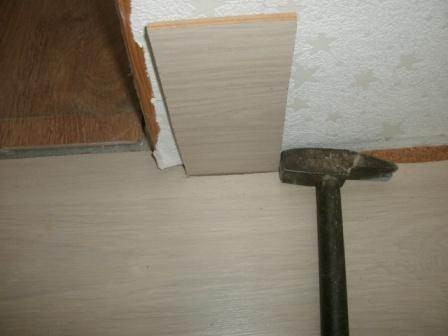 Укладка ламината под дверью при помощи вспомогательных средств
